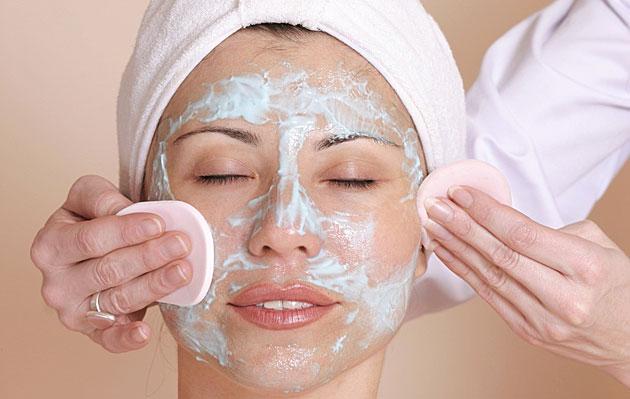 Foto: Portraitaufnahme einer jungen Frau, der mit Wattepads Creme aus dem Gesicht entfernt wird. Bildquelle: Fotolia.de.