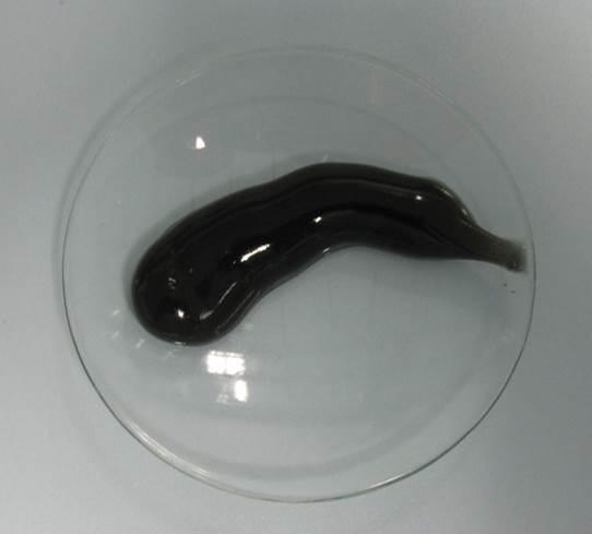 Schwarze Zahncreme auf einem Glas.