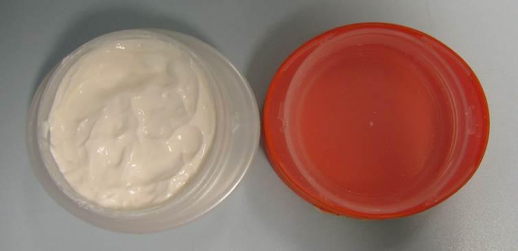 Tiegel mit Hautbleichmittelcreme und orangefarbenem Deckel.