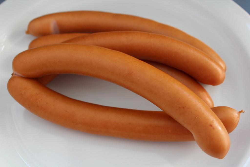 Gezeigt werden fünf ganze Wiener Würstchen mit Länge circa 17 cm auf einem weißen Teller liegend.