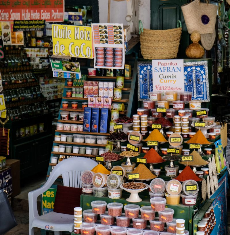 Auf dem Bild ist ein Straßenstand eines Basars in Tunesien mit vielfältigen Gewürzen zu sehen. Schilder an der Ware bezeichnen die Produkte als Paprika, Safran, Curry und weitere.