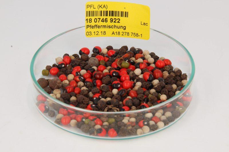 Das Bild zeigt eine Petrischale mit einer Pfeffermischung bestehend aus schwarzen, weißen, grünen und roten Körnern. Ein Aufkleber auf der Schale gibt die Probenidentifikationsnummer mit Barcode an.