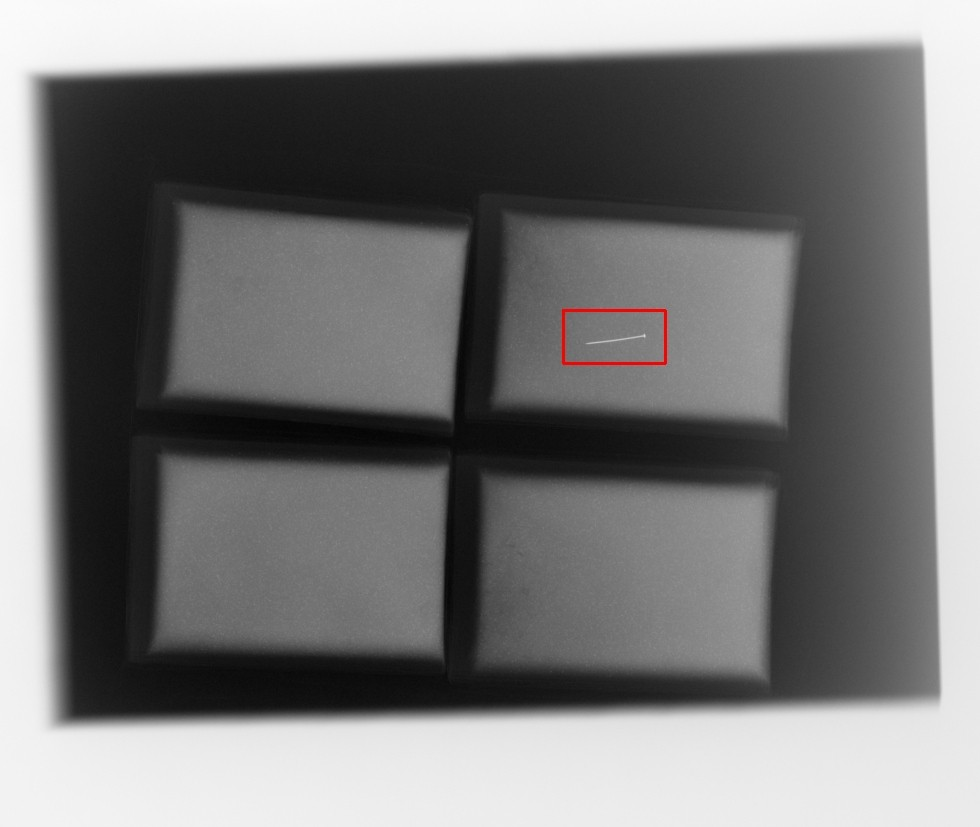Röntgenbild von vier Pulverpackungen, wobei die Stecknadel unter die Pulverpackungen gelegt wurde. Somit Nachstellung einer Positivkontrolle.