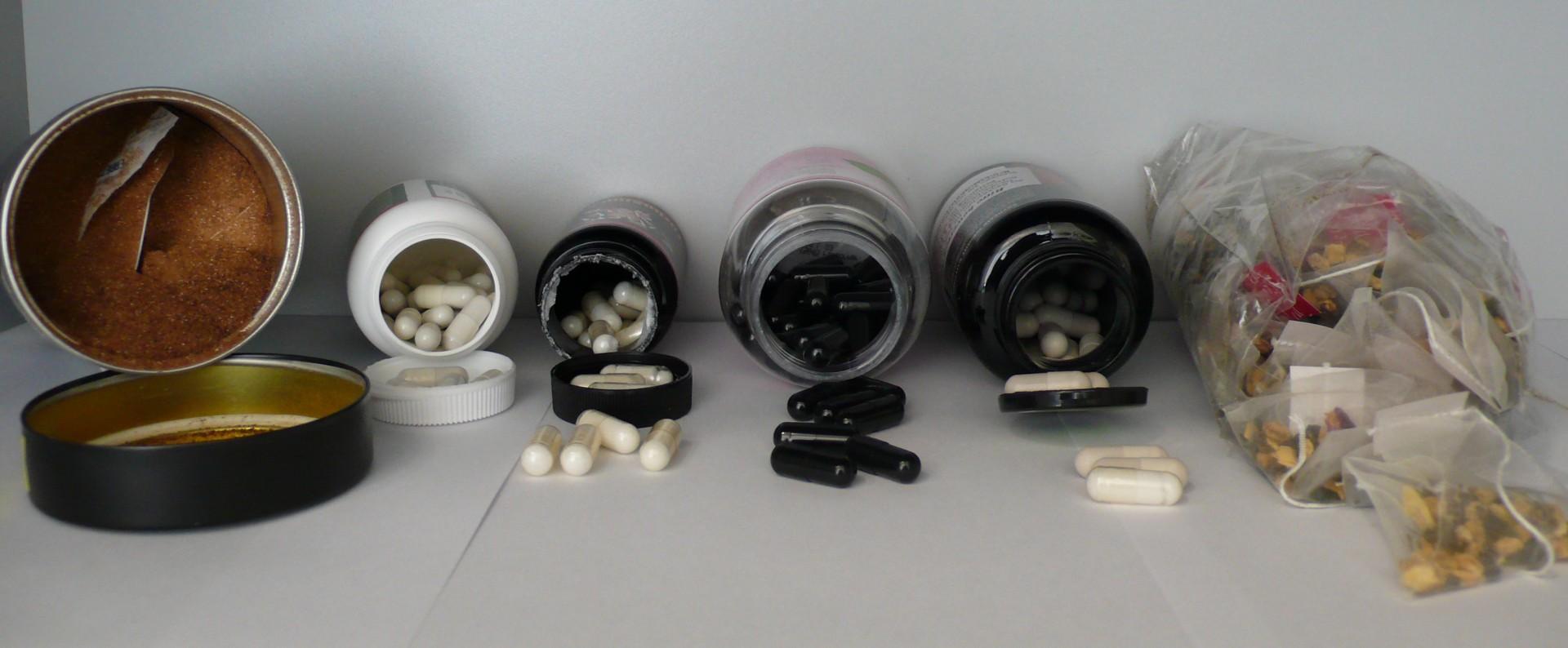 Das Bild zeigt verschiedenen offenen Verpackungen von Nahrungsergänzungsmitteln in Kapselform, sowie eine Kaffeedose mit Pulver und mehrere Teebeutel.