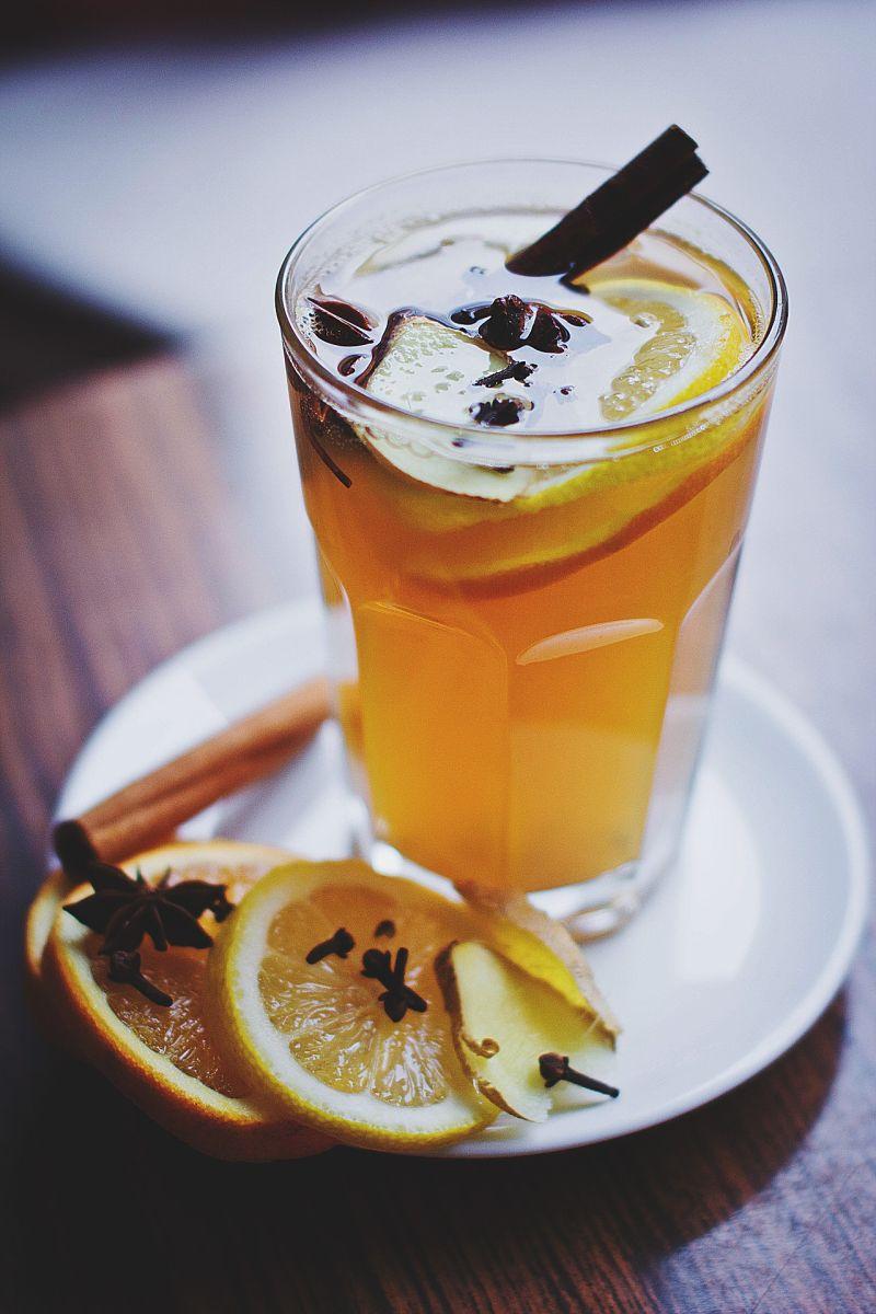 Das Bild zeigt ein gelb-farbenes Punschgetränk in einem Glas, garniert mit Orangenscheiben, Nelken und Zimtstangen.