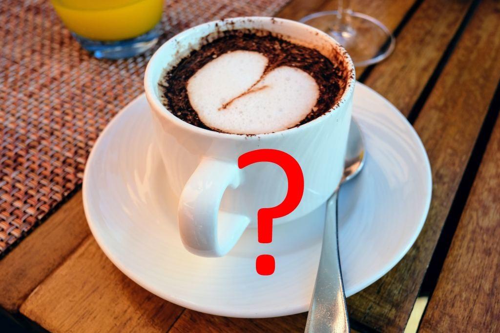 Auf dem Bild ist eine Tasse mit Milchschaum zu erkennen. Auf der Tasse ist ein Fragezeichen abgebildet.