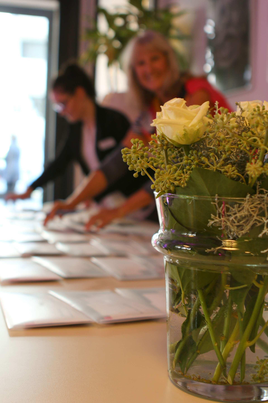 Empfang des Karlsruher Kosmetik Tages 2016. Im Vordergrund ein Blumenstrauß in einer Vase und im Hintergrund bereiten zwei Mitarbeiter des CVUA Karlsruhe die Informationsunterlagen vor.