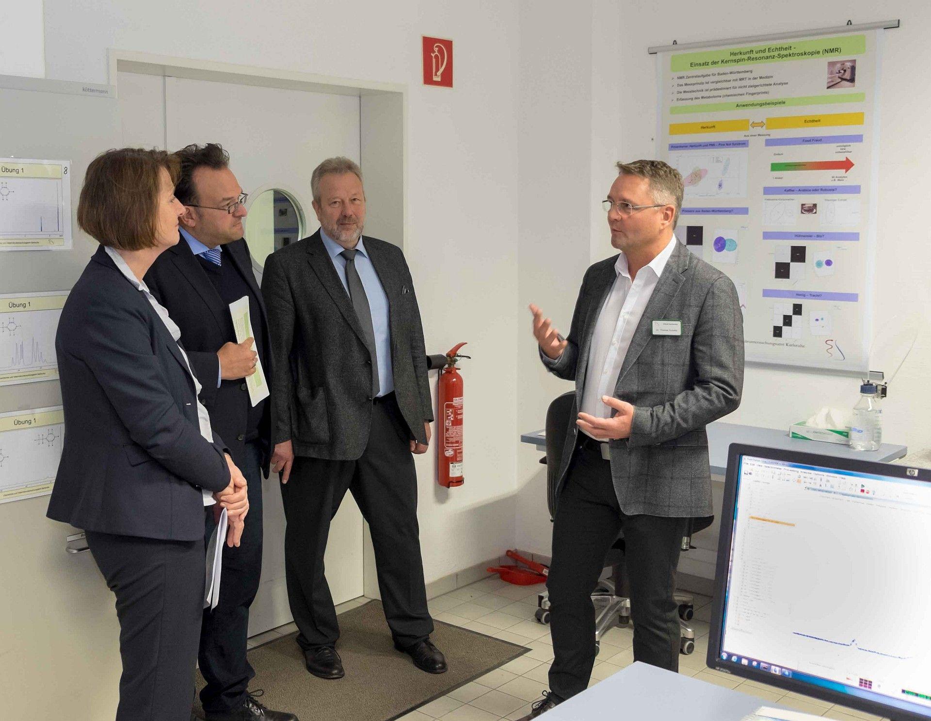 Von links nach rechts im Bild Frau Leukhardt, Herr Walch (Dienststellenleiter des CVUA Karlsruhe), sein Vertreter Herr Dr. Marx und Herr Dr. Kuballa. Der Leiter des NMR-Teams. Im Hintergrund sind Poster mit Themen der NMR-Diagnostik erkennbar.