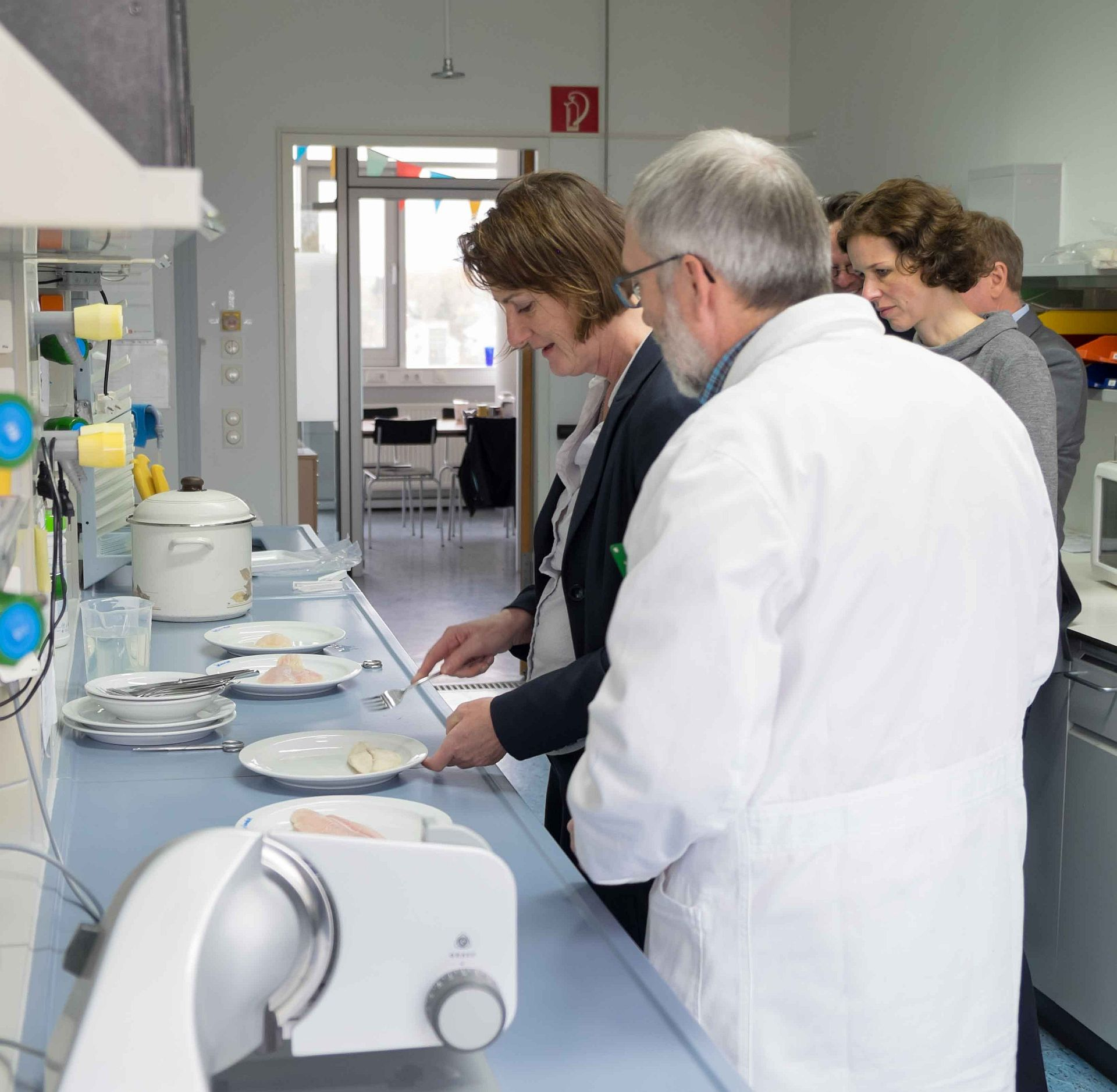 Das Bild zeigt Frau Leukhardt mit einer Gabel in der Hand bei der Verkostung einer Reihe von durcherhitzten Fischfilets. Die Filets sind auf Tellern auf einem Labortisch angerichtet. Daneben steht eine Gruppe weiterer Personen.