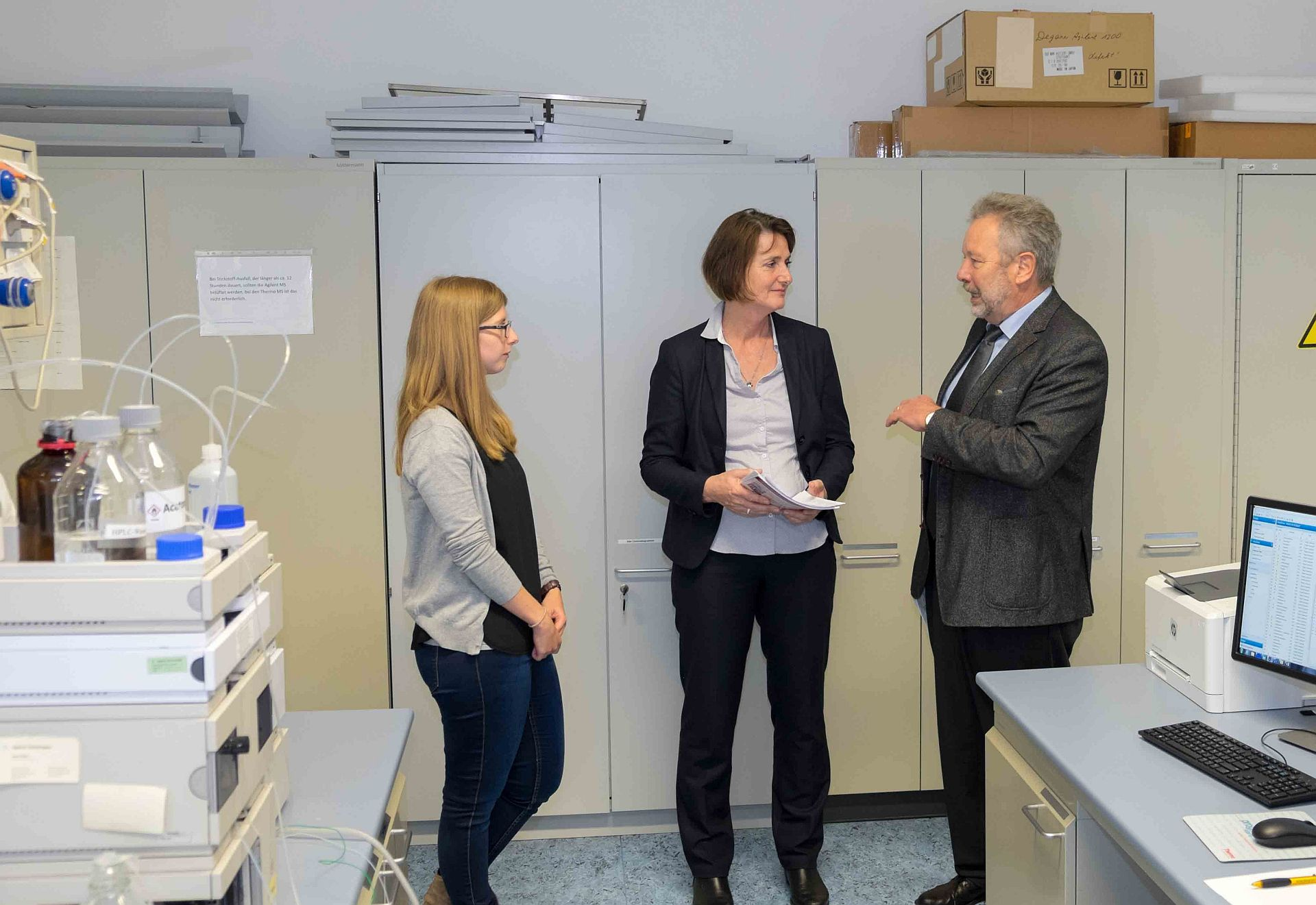 Herr Dr. Marx der stellvertretende Dienststellenleiter des CVUA Karlsruhe (rechts im Bild) und eine Mitarbeiterin der Abteilung 3 (Mitte) stellen FrauLeukhardt (rechts im Bild) die Aufgabengebiete des NRKPs in den Räumlichkeiten der Abteilung für pharmakologisch wirksame Rückstände des CVUA Karlsruhe vor.