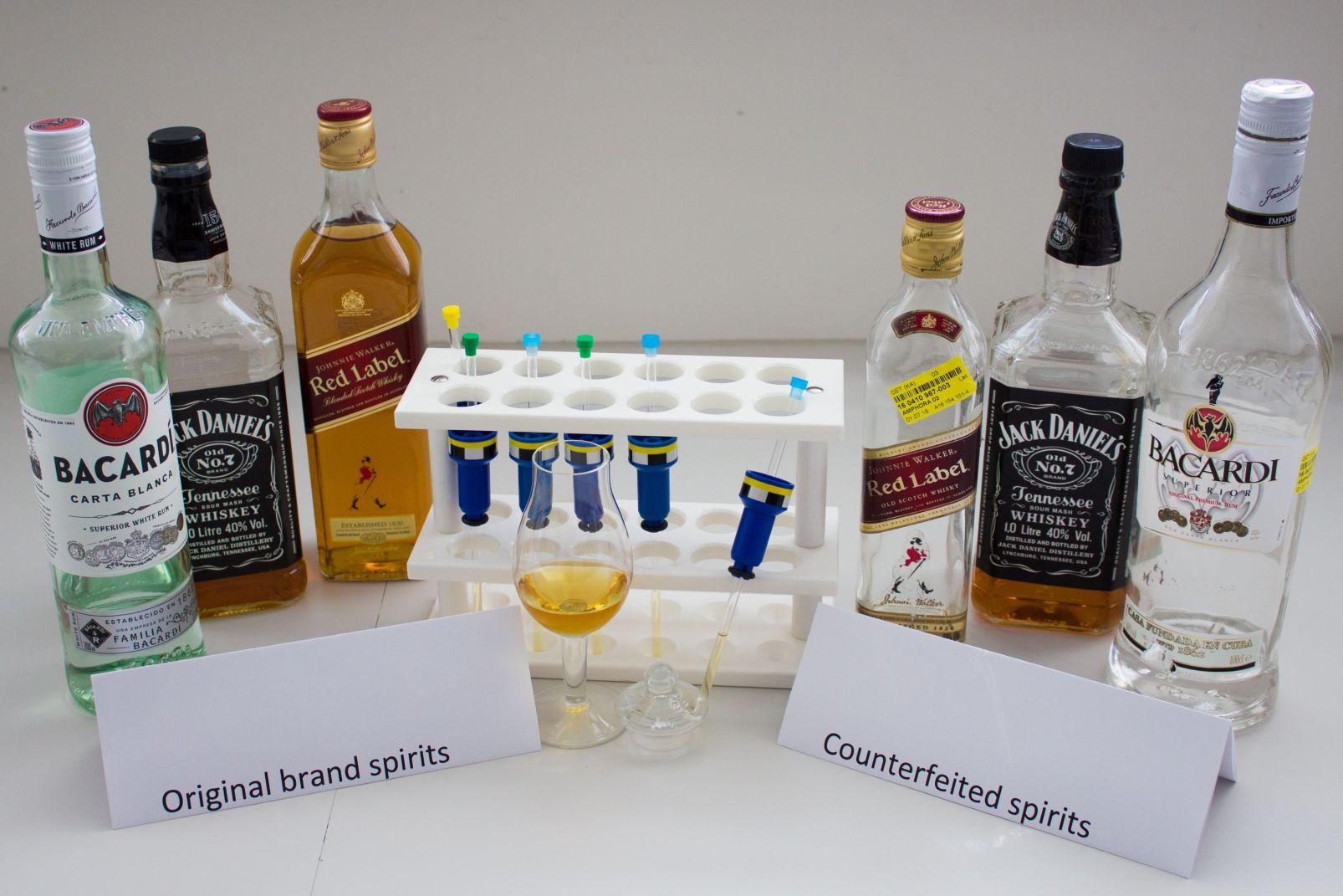 Das Foto zeigt originalverpackte Spirituosenflaschen bekannter Marken und daneben,   nicht unterscheidbar die Fälschungen dieser Produkte. In der Mitte des Bildes befindet sich ein Reagenzglasgestell mit gefüllten Messröhrchen für die NMR Messung und im Vordergrund ein Glas mit Whiskey.