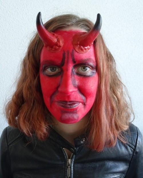 Das Bild zeigt ein Mädchen mit schwarz-rot-geschminktem Gesicht und Verkleidung als Teufelchen.